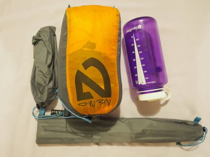 Nemo Equipment Blaze 2p Tent fly and and body stuffed with pegs and poles removed compared with a 1 liter water bottle.