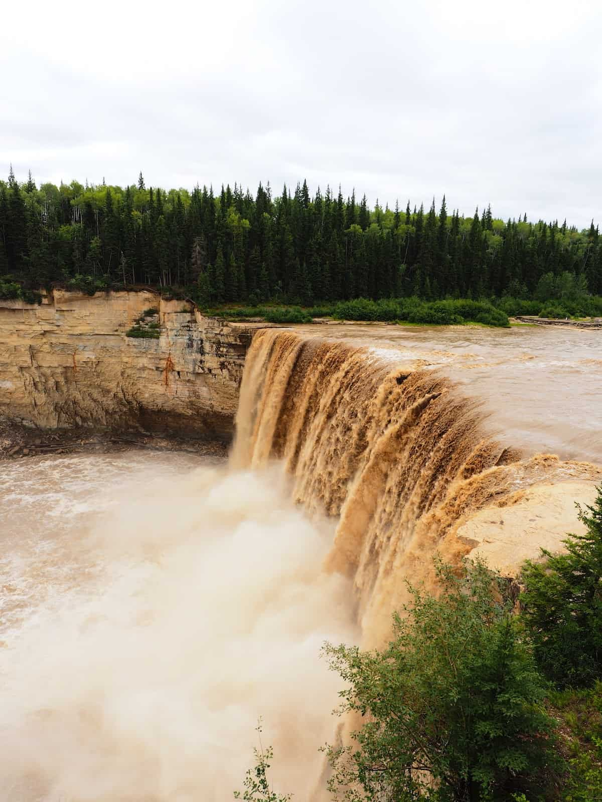 Nahanni River by Canoe: A muddy river crests over a waterfall