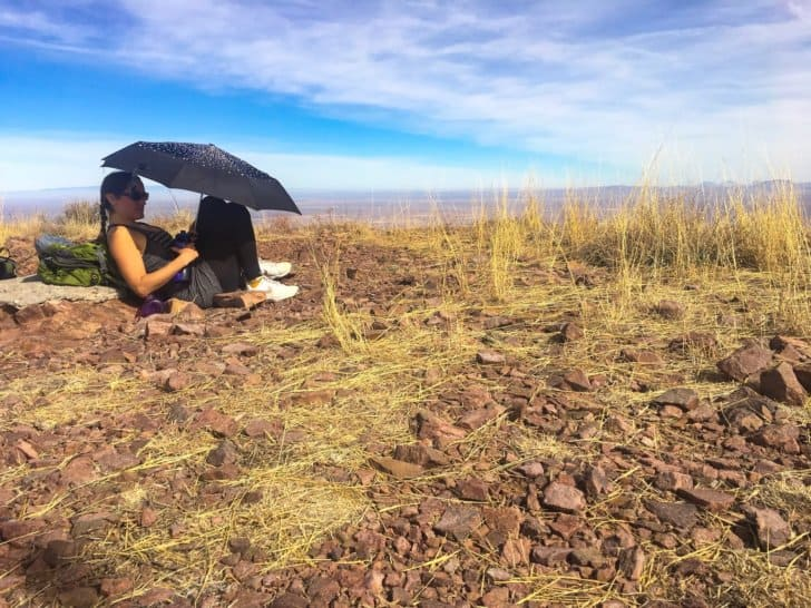 relationship while backpacking: hiding from the sun under an umbrella