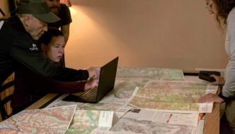 hikers planning a backpacking trip with maps and a computer