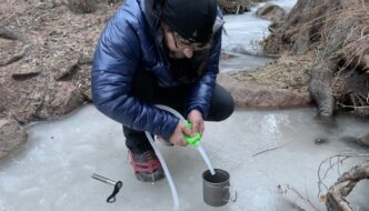 ryan using a suction tube to get water out of a frozen creek