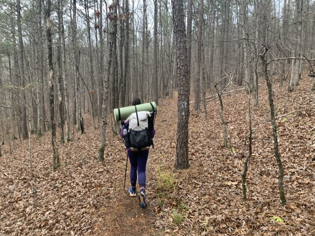 A backpacking confession: Maggie walking through the woods with her foam pad