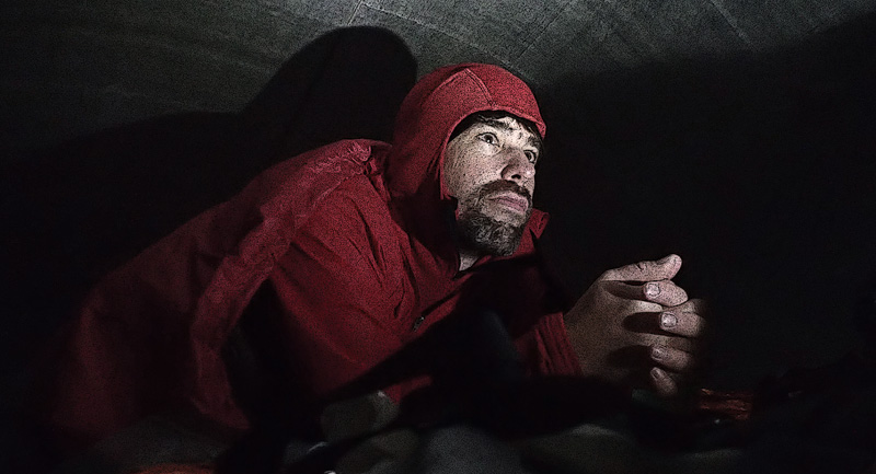a sad-looking man rests in a tent