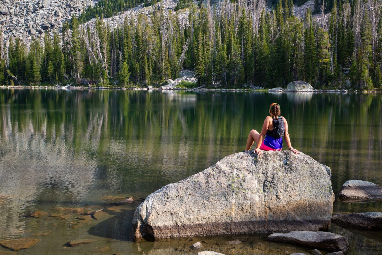 A woman sits on a boulder at the shores of an alpine lake, looking across the water.