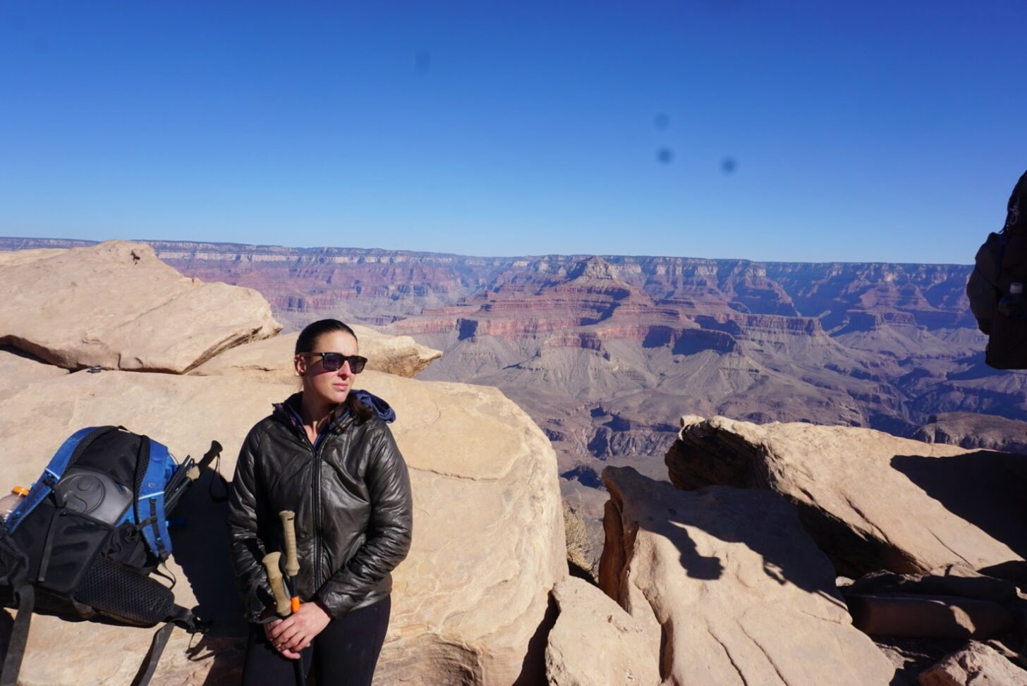 A woman in sunglasses sits on a ledge above the grand canyon