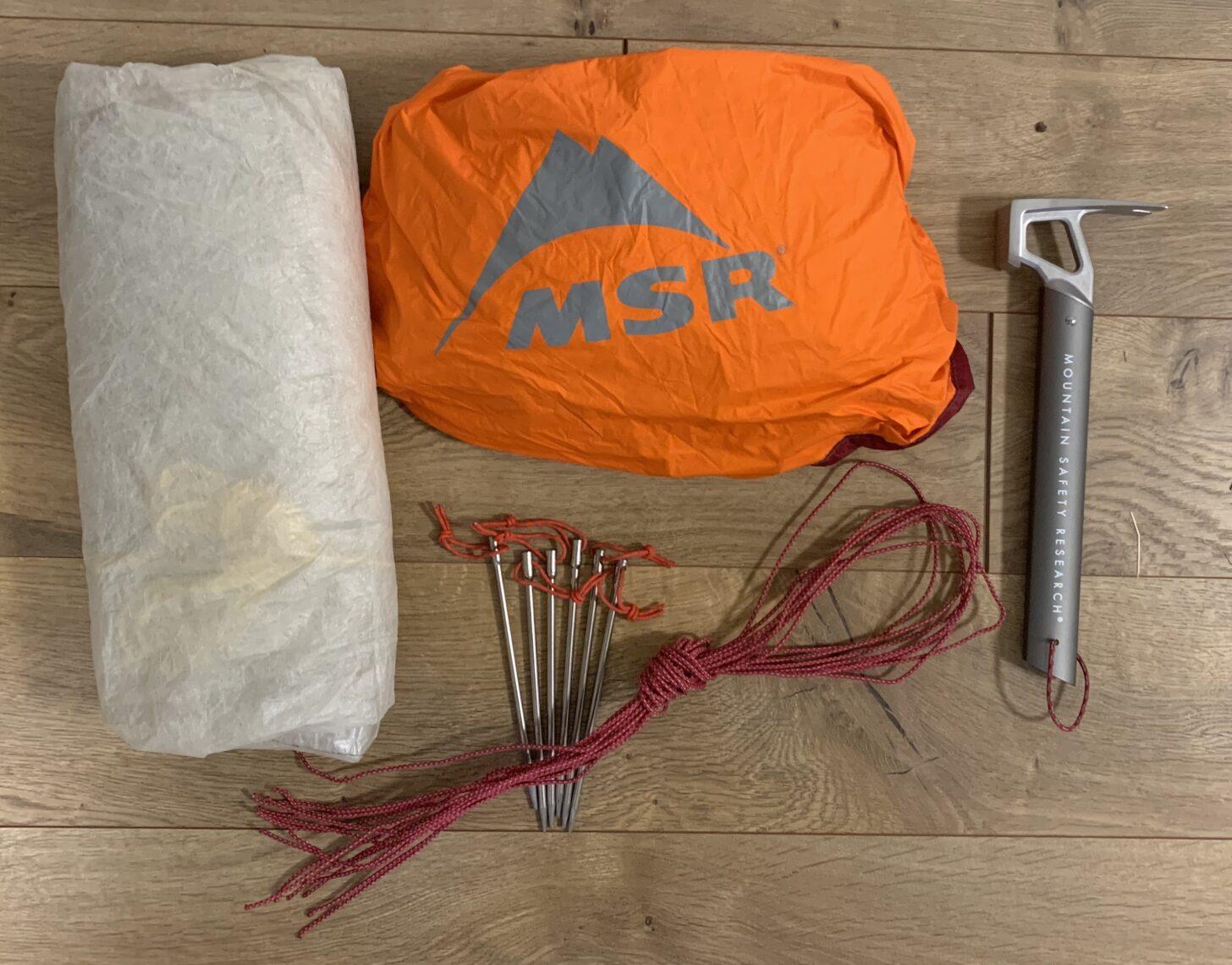 tarp, bivy sack, nail stakes, extra guylines, and a stake hammer