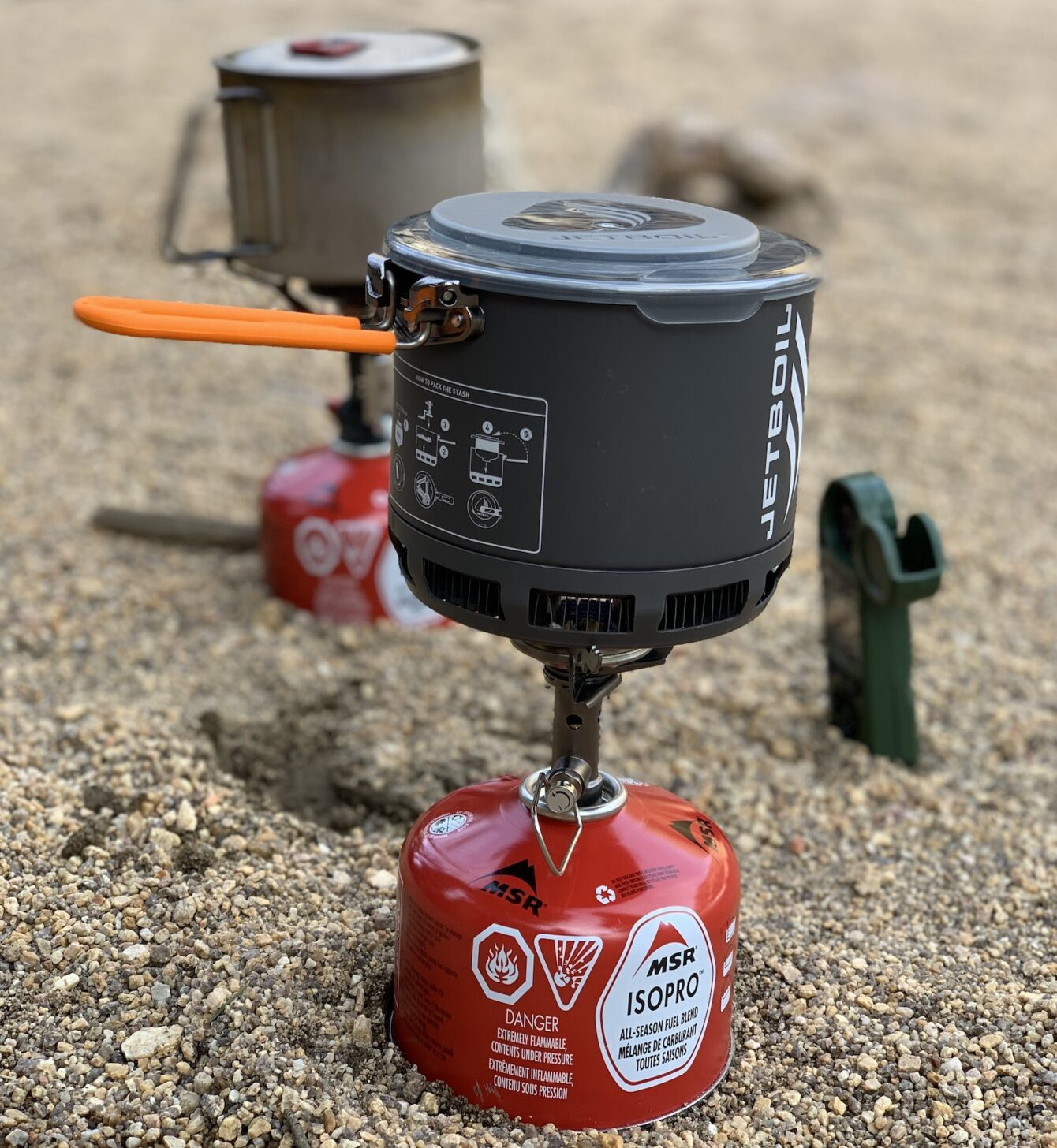 two isobutane canister stove cooking systems side by wide with a wind meter, for a comparison test