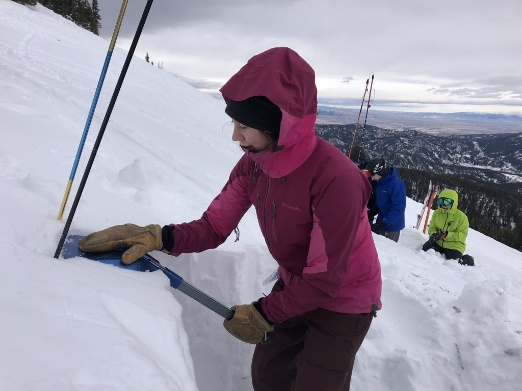 a woman digs a hole in the snow on a steep mountainside