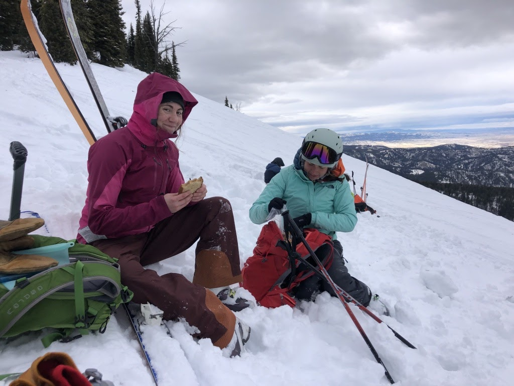 a woman eats a sandwich while sitting in snow on the side of a mountain