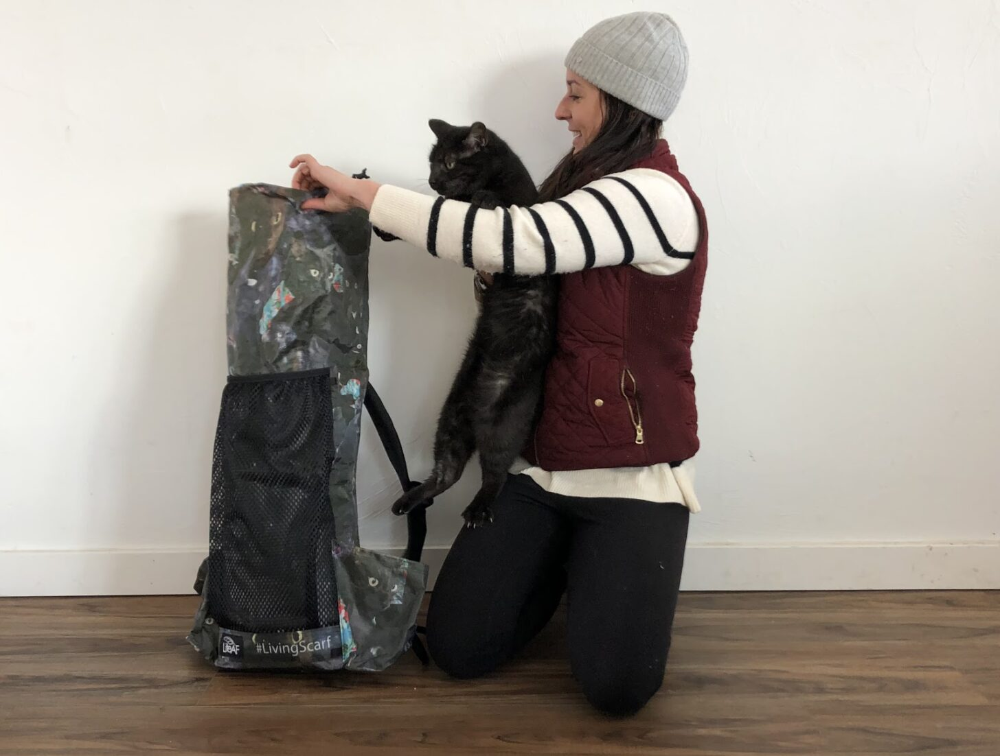 a woman trying to stuff a cat into a backpack
