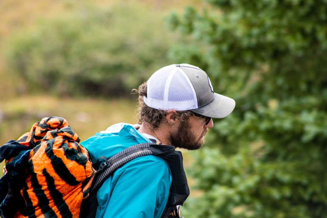 a man hiking with a tiger-striped backpack