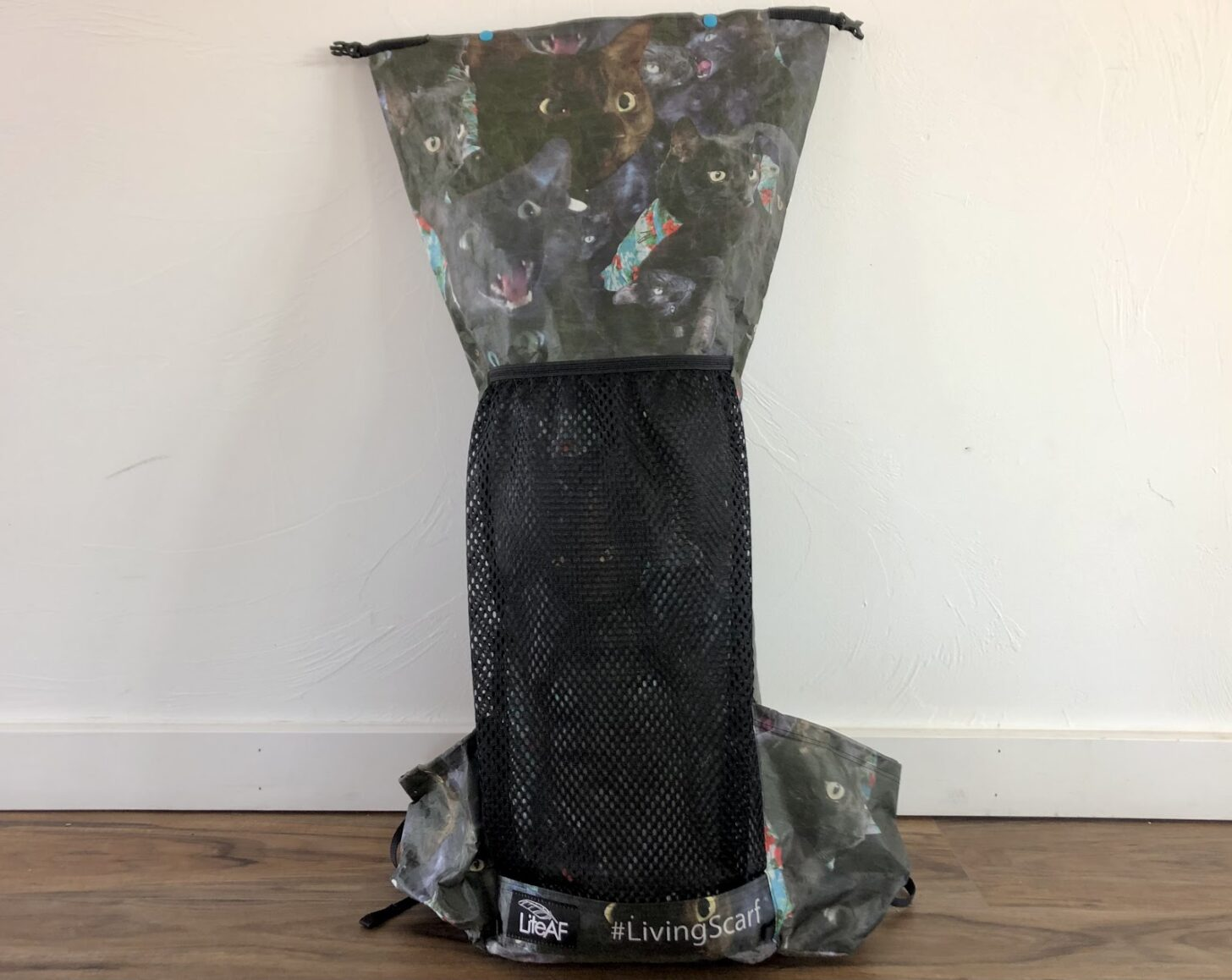a backpack with a collage of cat faces printed on it.