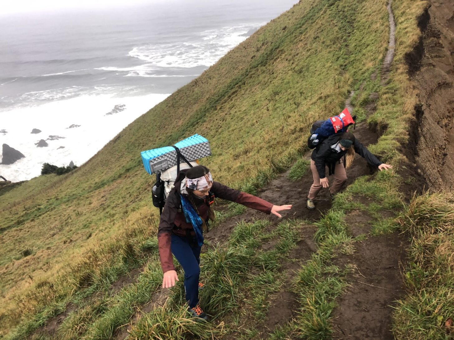 two women struggle up a steep slope with the ocean in the background.