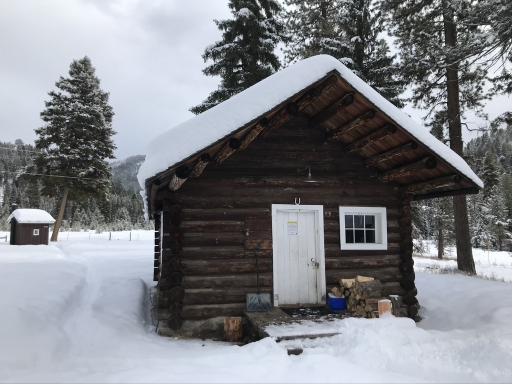 a backcountry cabin covered in snow
