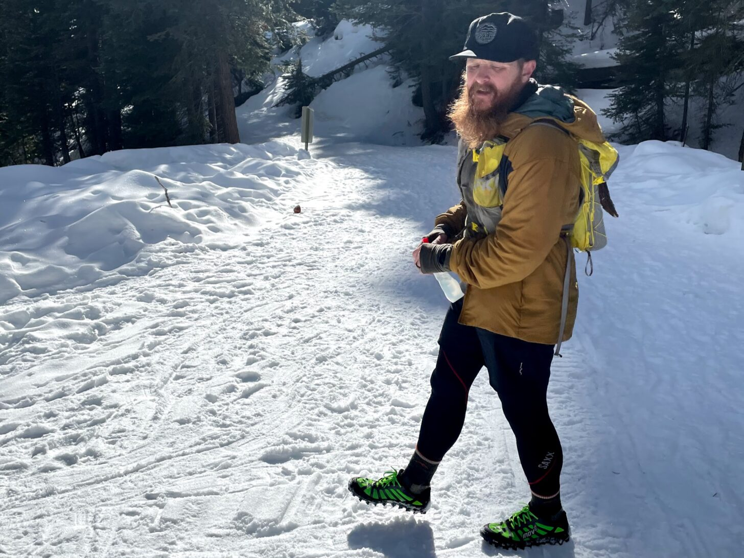 a luxuriously bearded man rests after running up a snowy hill