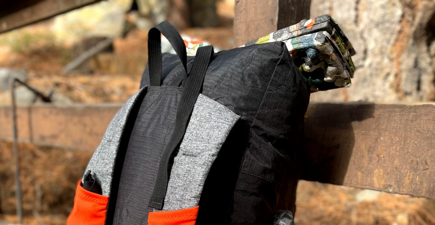 a sit pad strapped atop a backpack