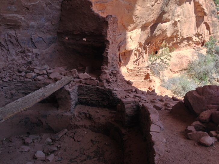 some ruins in shade beneath an overhanging cliff