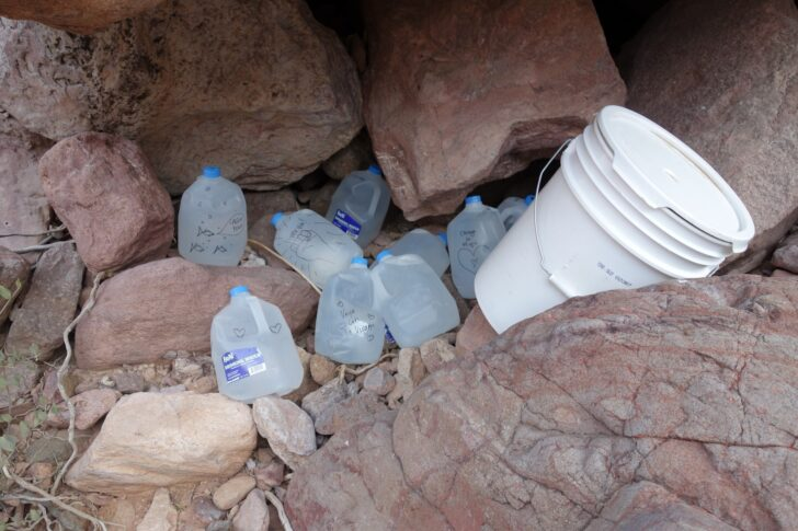 a pile of one-gallon water jugs
