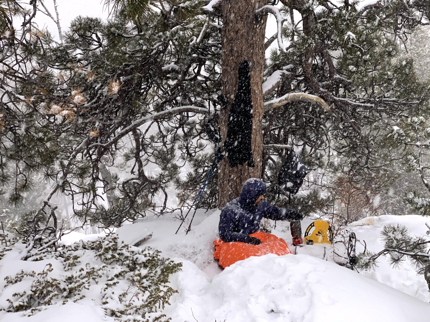 man in bivy sack during a snow storm