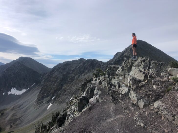 a woman stands on top of a mountain