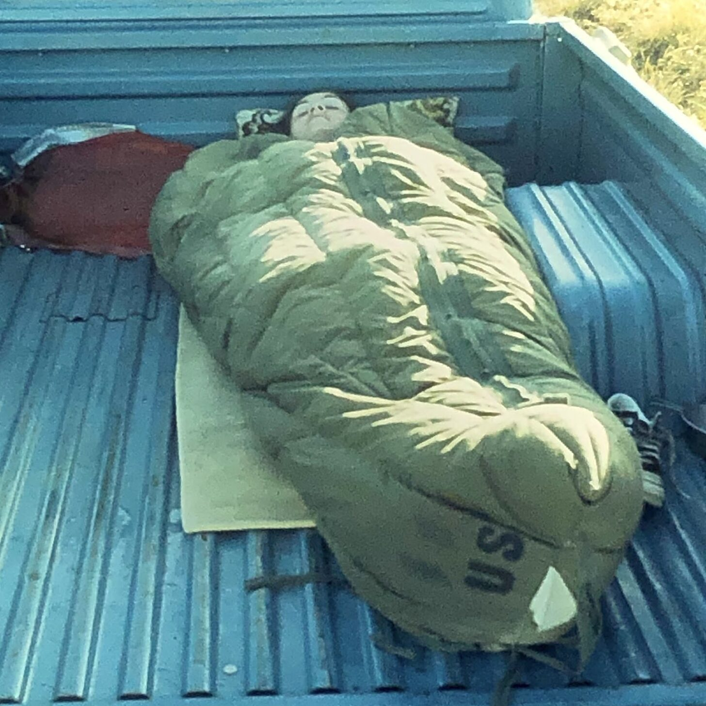 a person sleeping in an old army surplus sleeping bag in the back of a truck.