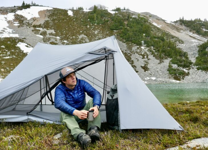 a man sits inside a tent drinking a cup of coffee with mountains in the background.