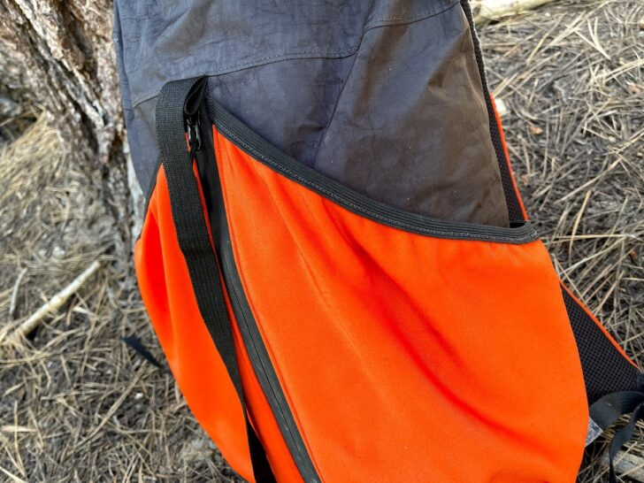 a medium shot showing the orange rear pockets cut at a sharp angle and angling down towards the sides of the pack.