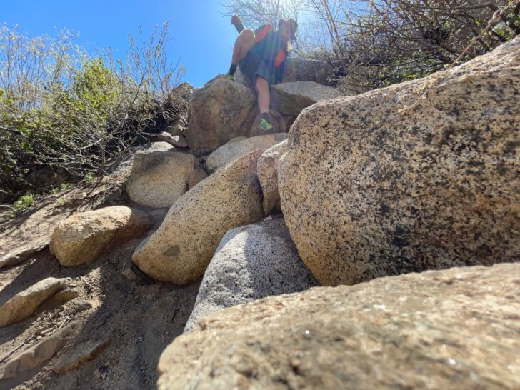 a man picks his way down a rocky slope while wearing an orange backpack.