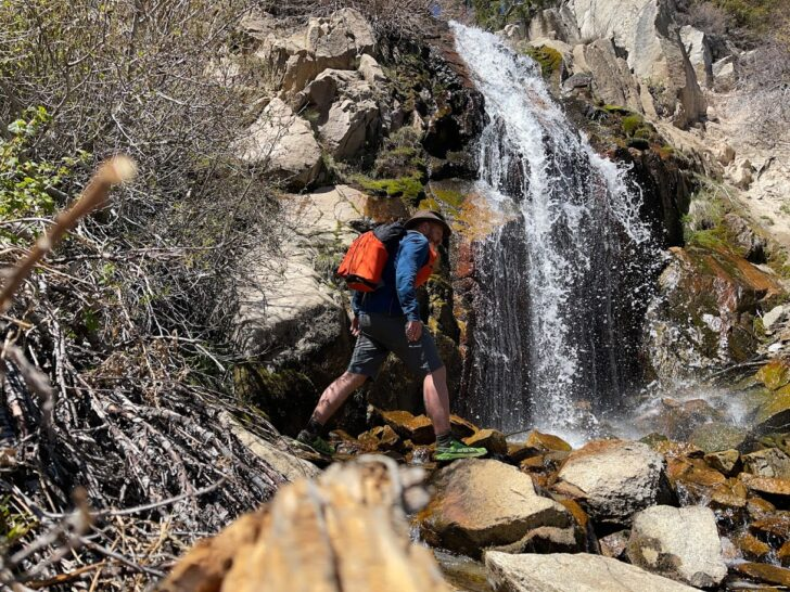 a man works his way underneath a waterfall while wearing an orange backpack.
