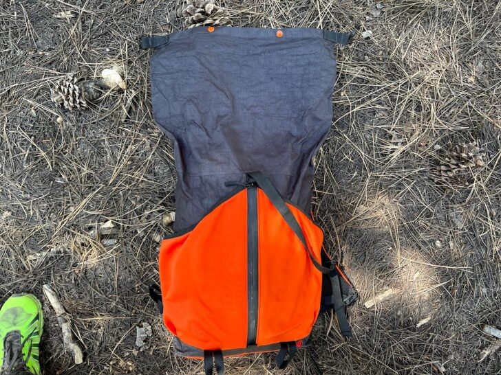 a medium shot showing the pack on the ground with the roll-top compartment fully unrolled.