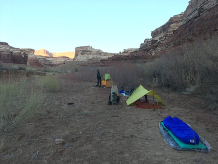 a campsite with multiple setups - a cowboy setup, a tarp, and a fully enclosed shelter. There are desert mountains in the background.