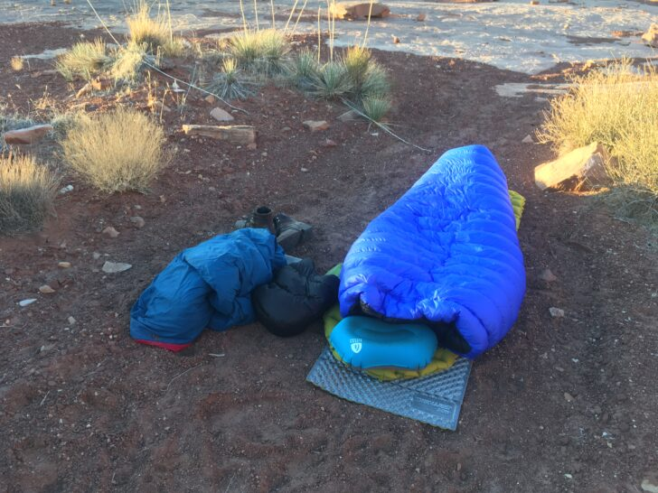 a blue quilt laid over a sleeping pad. In the background, ice and snow is on the ground.