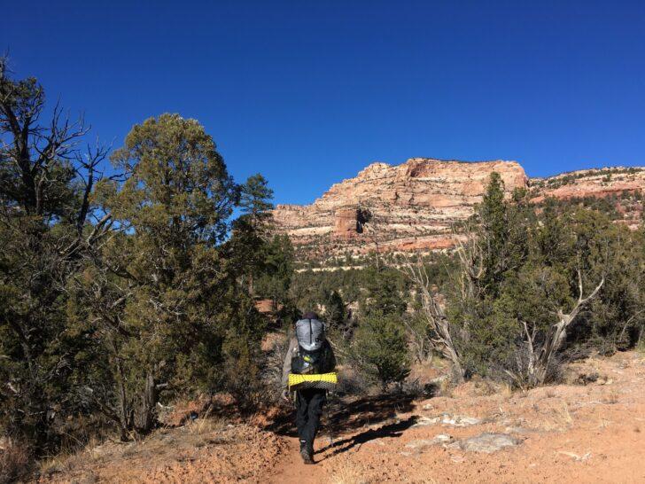 a man backpacks through the Utah desert