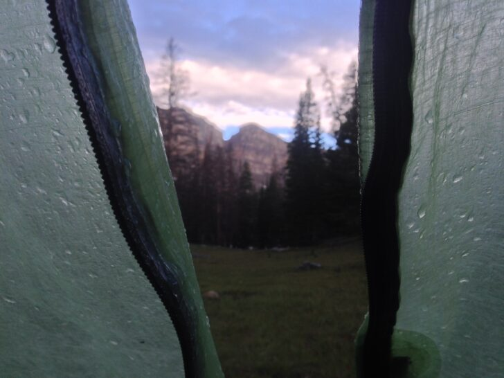 a view of mountains at sunrise from within a tent