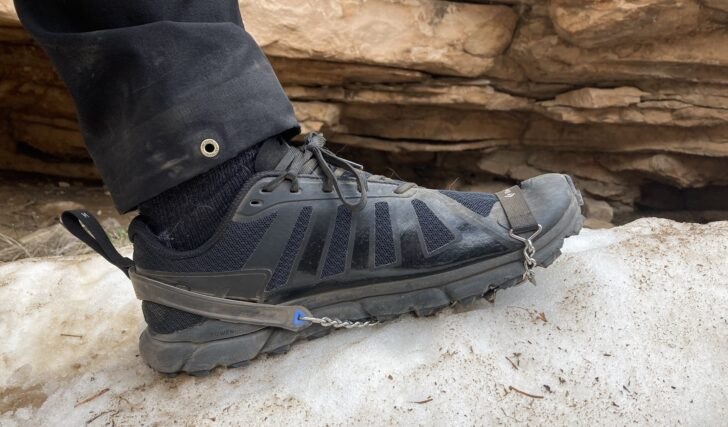 traction spikes on a trail running shoe in the snow