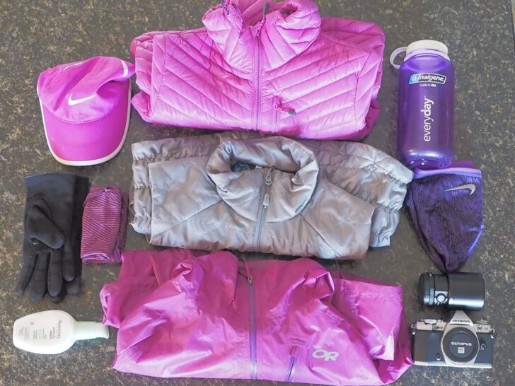 a flat layout of the backpacking gear able to fit into the pack - including some jackets, a hat, gloves, sunscreen, a small camera, and a hard-sided water bottle.