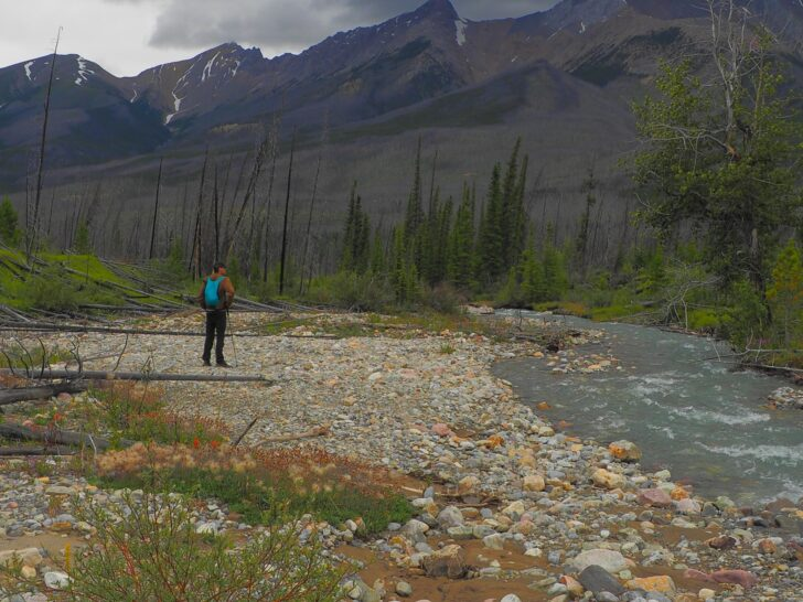 A man looks across a wide stream. In the background are rugged mountains and dark skies.