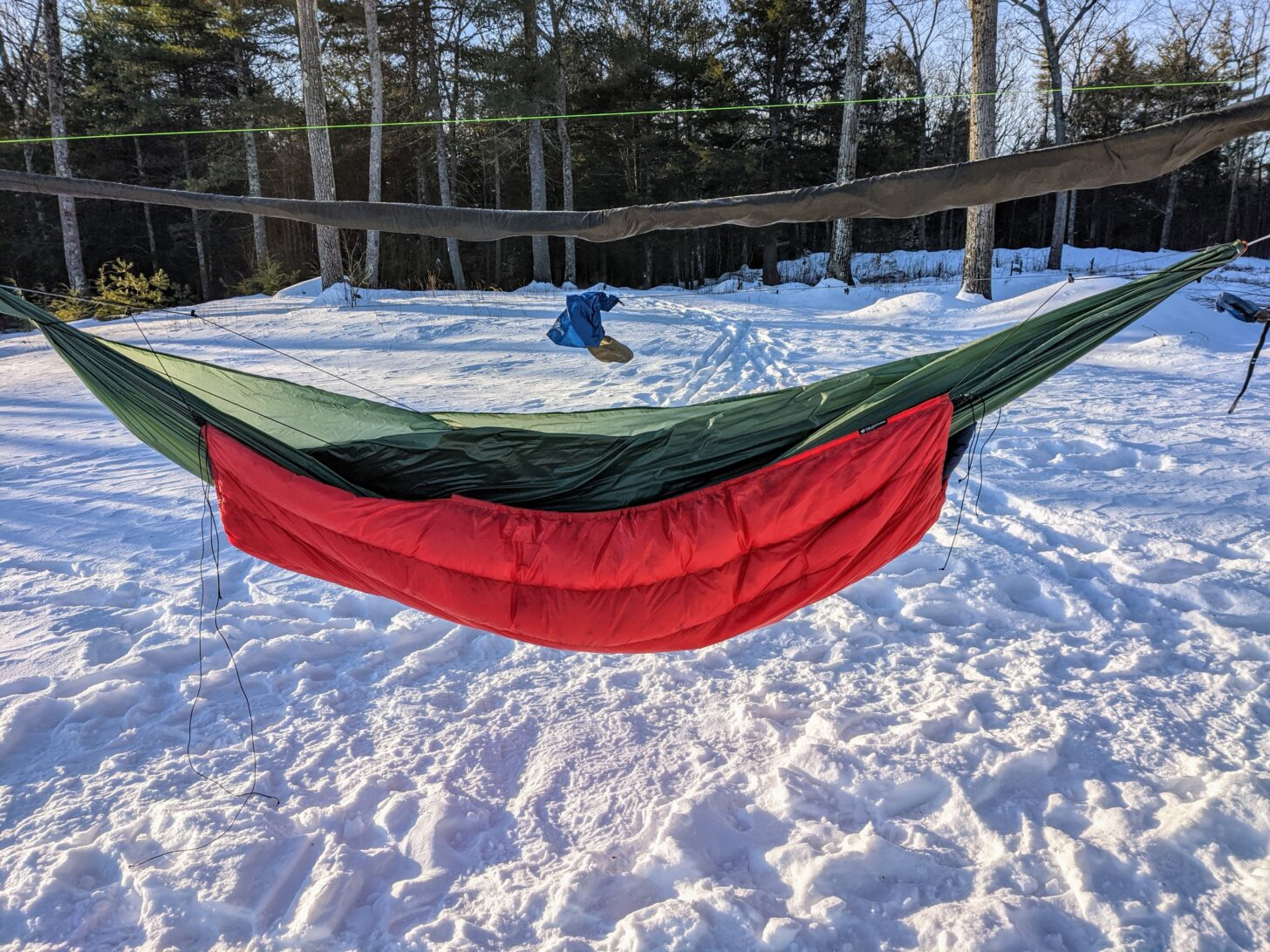 a red underquilt wraps a green hammock in a snowy forest
