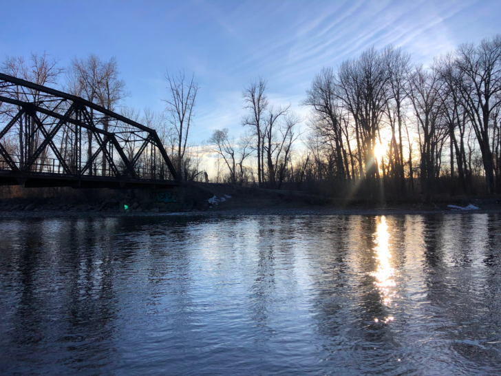 The sun rises over a deceptively calm river.