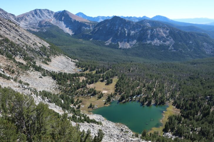 A wide landscape photo with mountains in the background. In the foreground, down in a valley, a blue lake sits like a gem in a green forest.