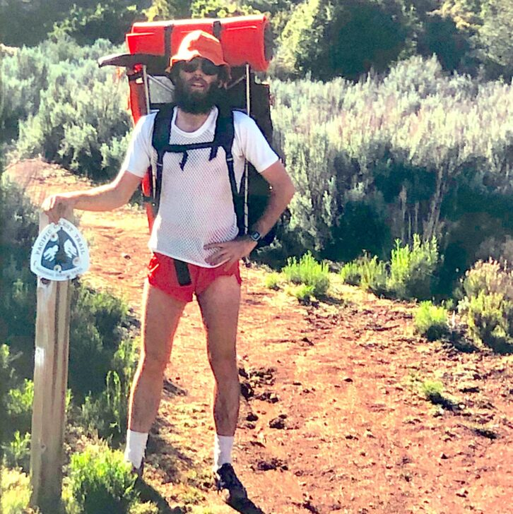 a skinny man with an oversized pack, a mesh shirt, and short shorts poses next to a trail sign for the PCT