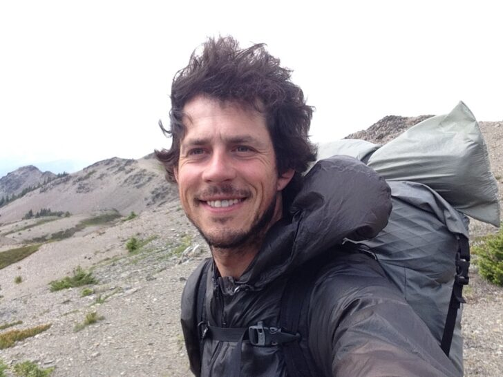 A man wearing a backpack smiles into the camera with wilderness behind him