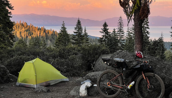 a bicycle and tent perched above a sunset