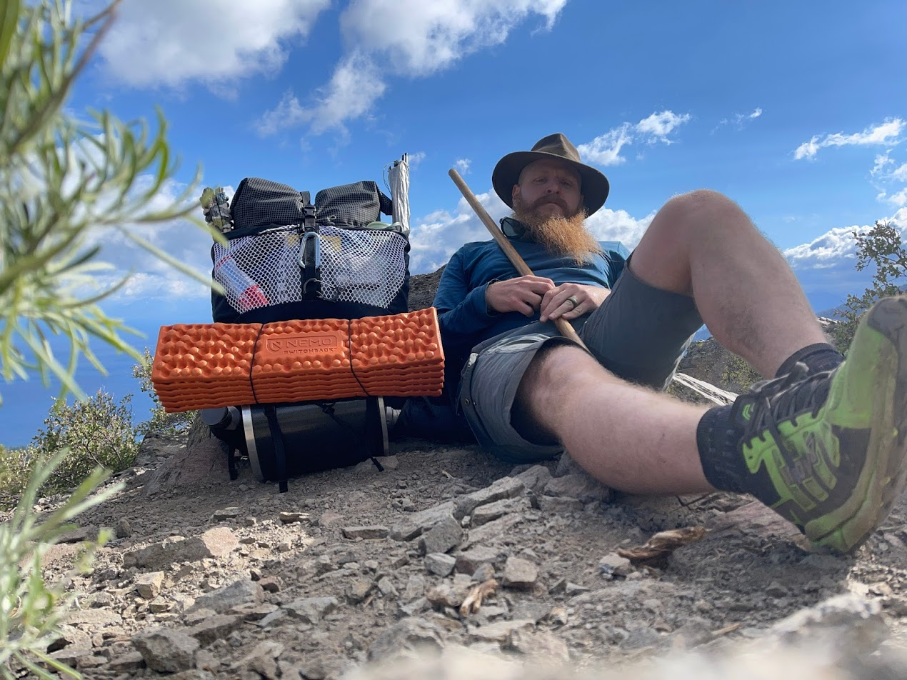 a man with a luscious red beard rests next to a fully loaded backpack.