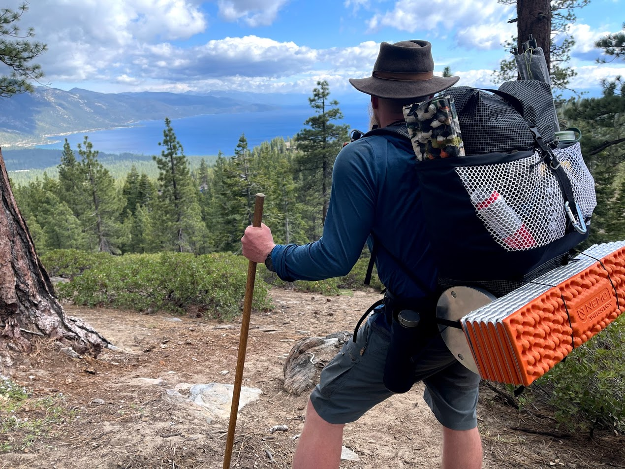 a rear view of a man wearing the backpacking, looking out over a view of a beautiful alpine lake.