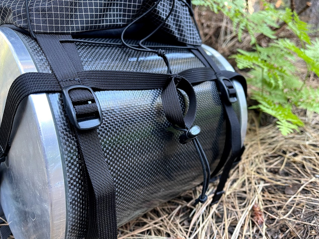A closeup of the system of webbing that allows the bear canister to slot into the pack.