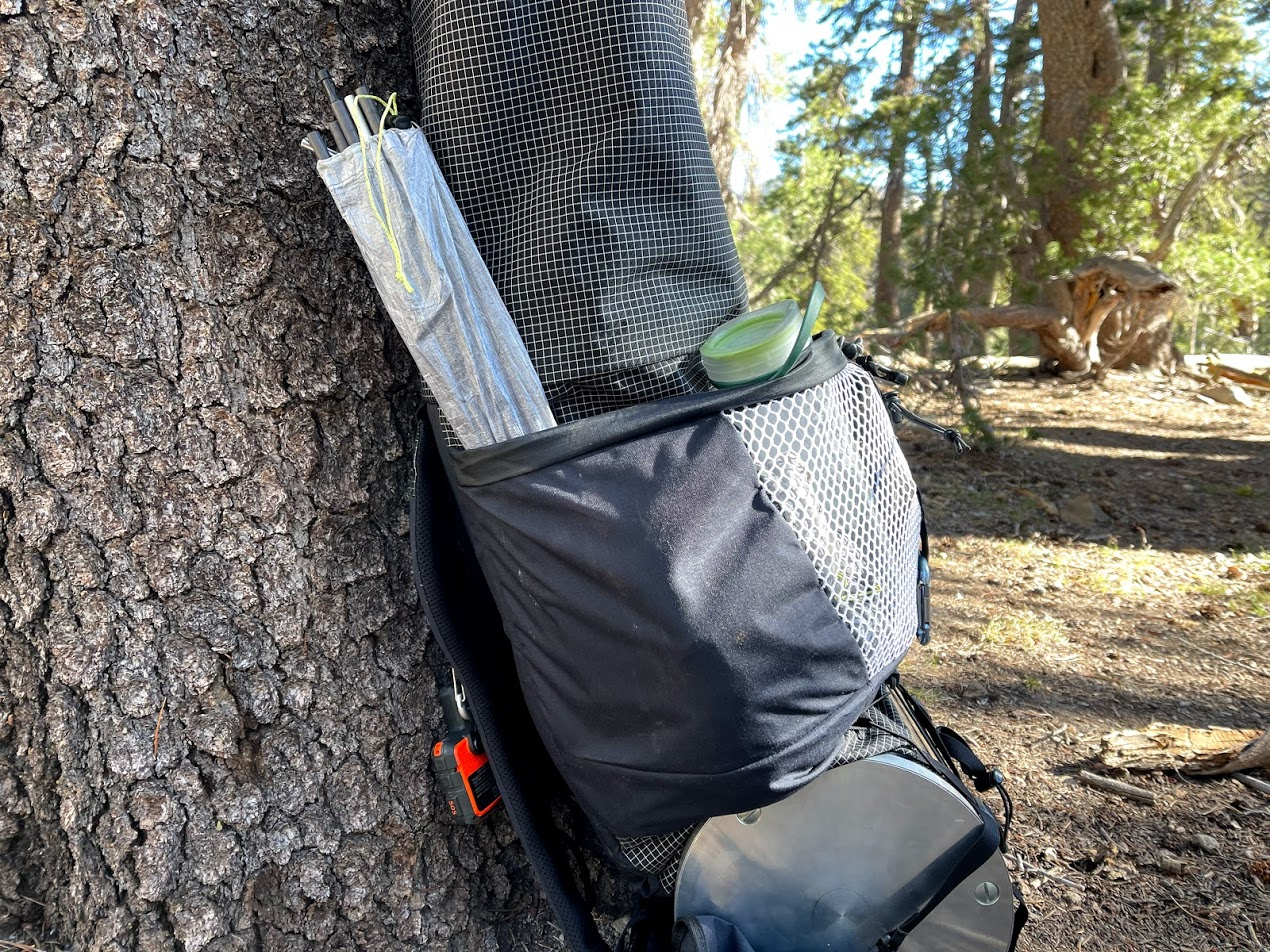 A medium shot of the pack, showing the wrap-around pockets, extended accordion-style closure, and bear canister storage.