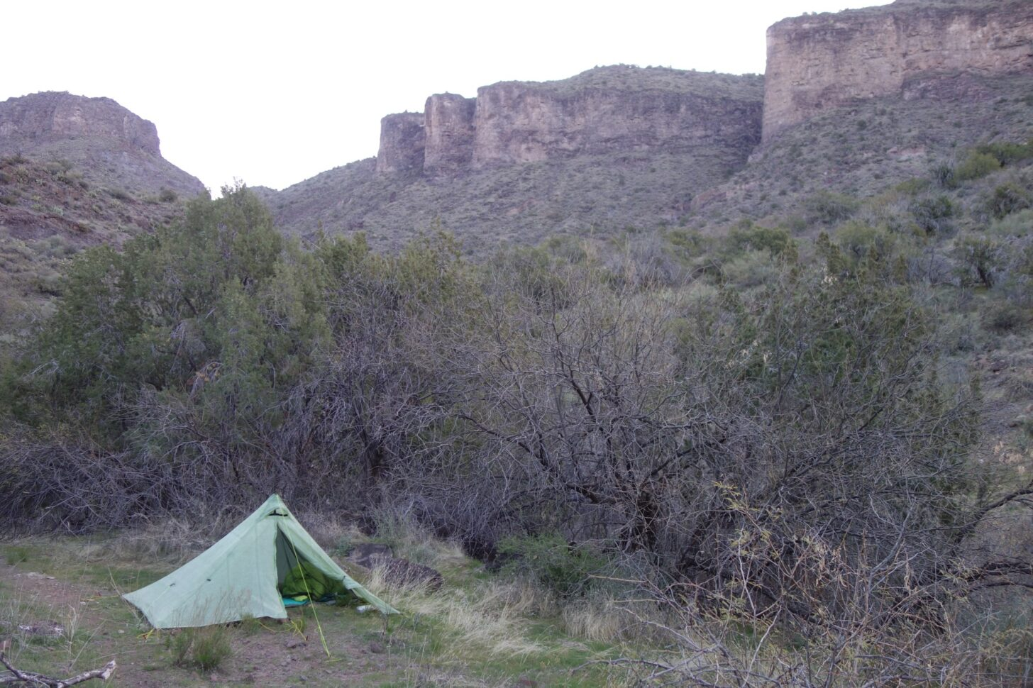 A pyramid style tent nestles into a hollow at the base of some cliffs.