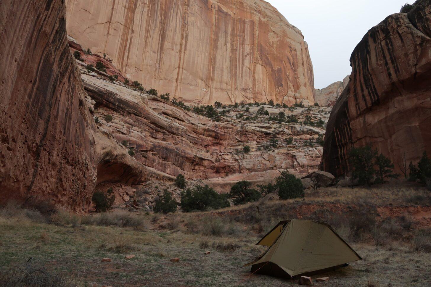 a small tent huddles beneath the sharply rising walls of a steep canyon.
