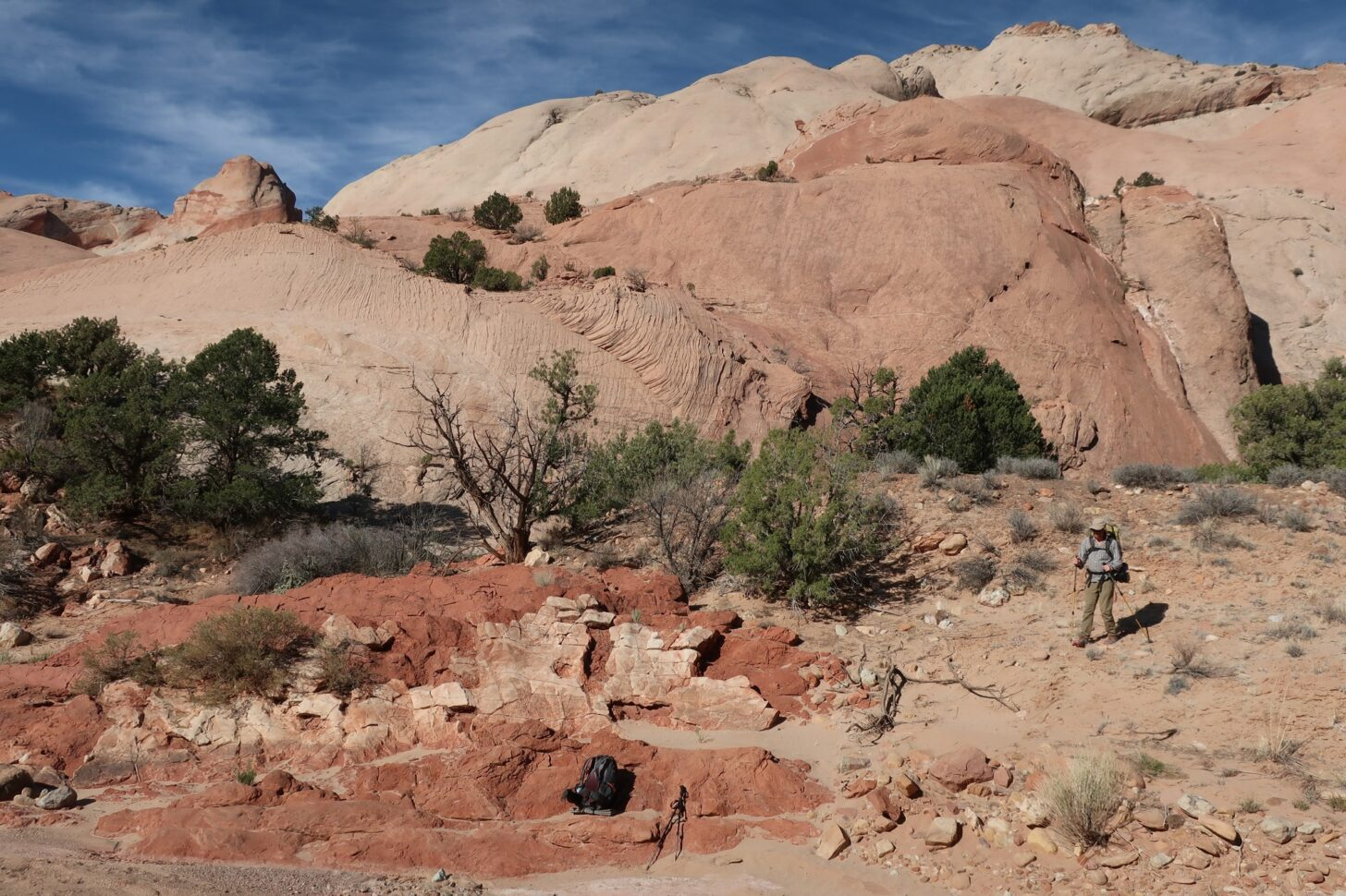 a small figure is dwarfed by piles and swirls of red and tan stone